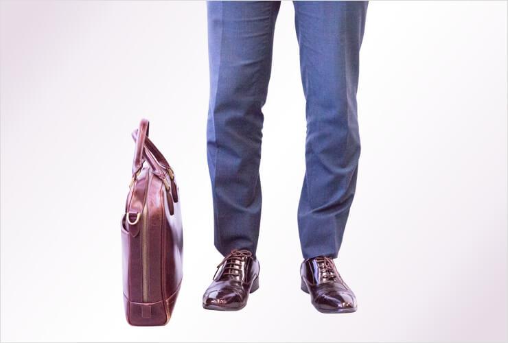 自立型の茶色いバッグと男性の足元