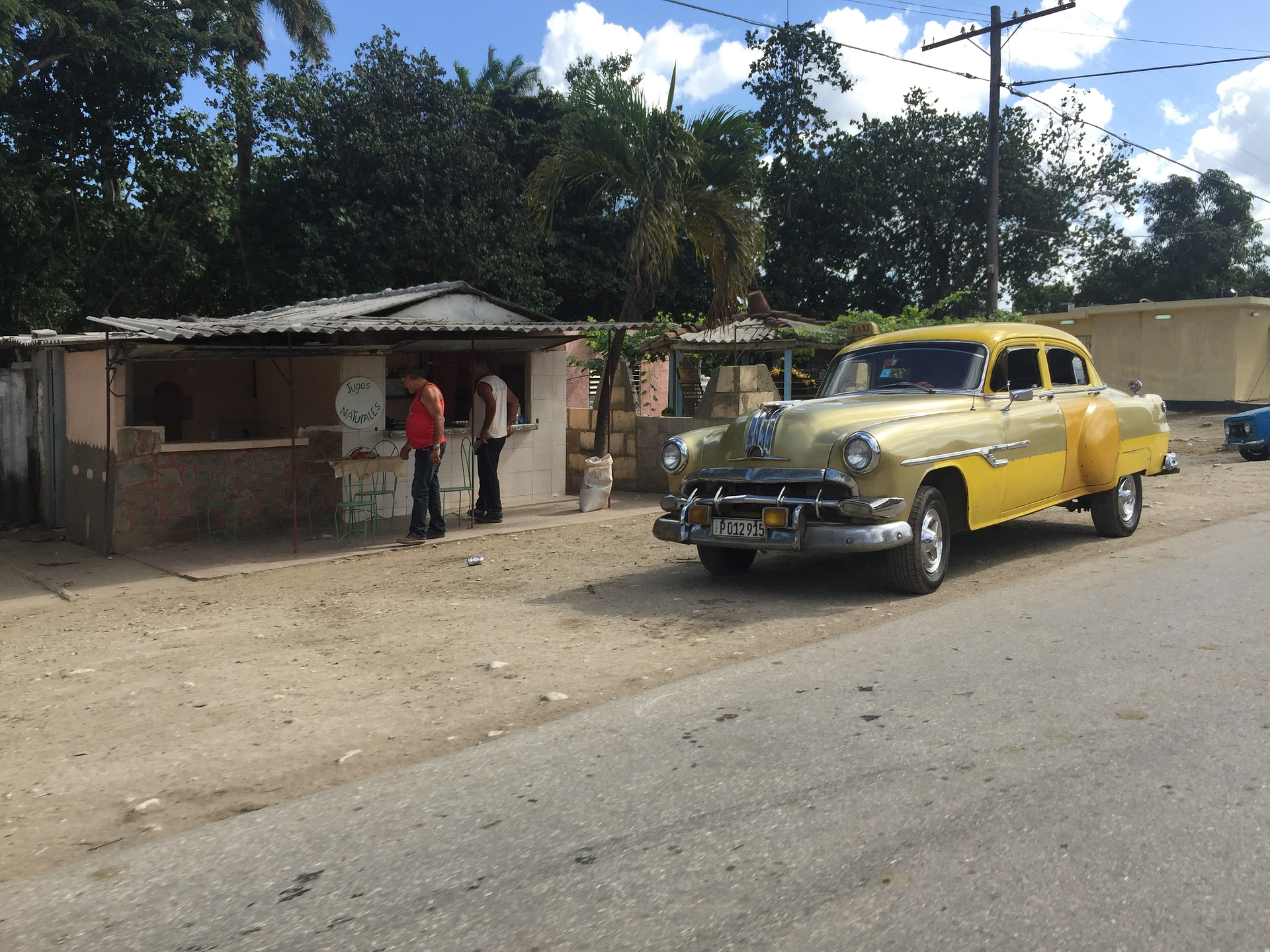 Yellow car in the road in Cuba driving