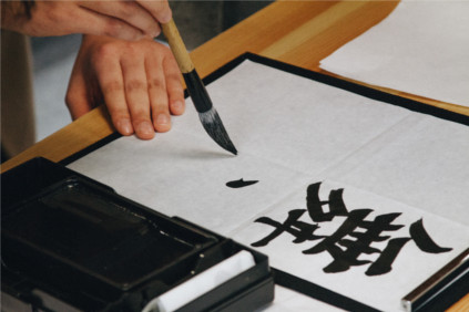 Person writing Japanese kanji with a brush