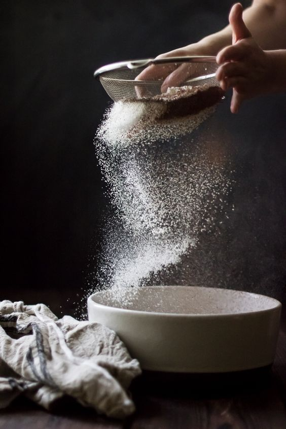 Sifting flour into white bowl